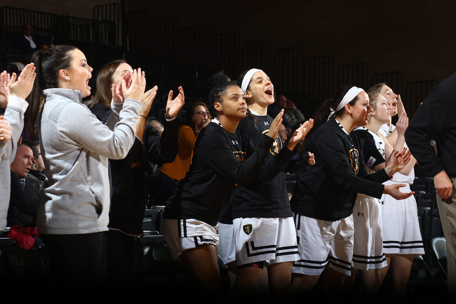 Women's basketball players cheer for their team members with fans in the background.