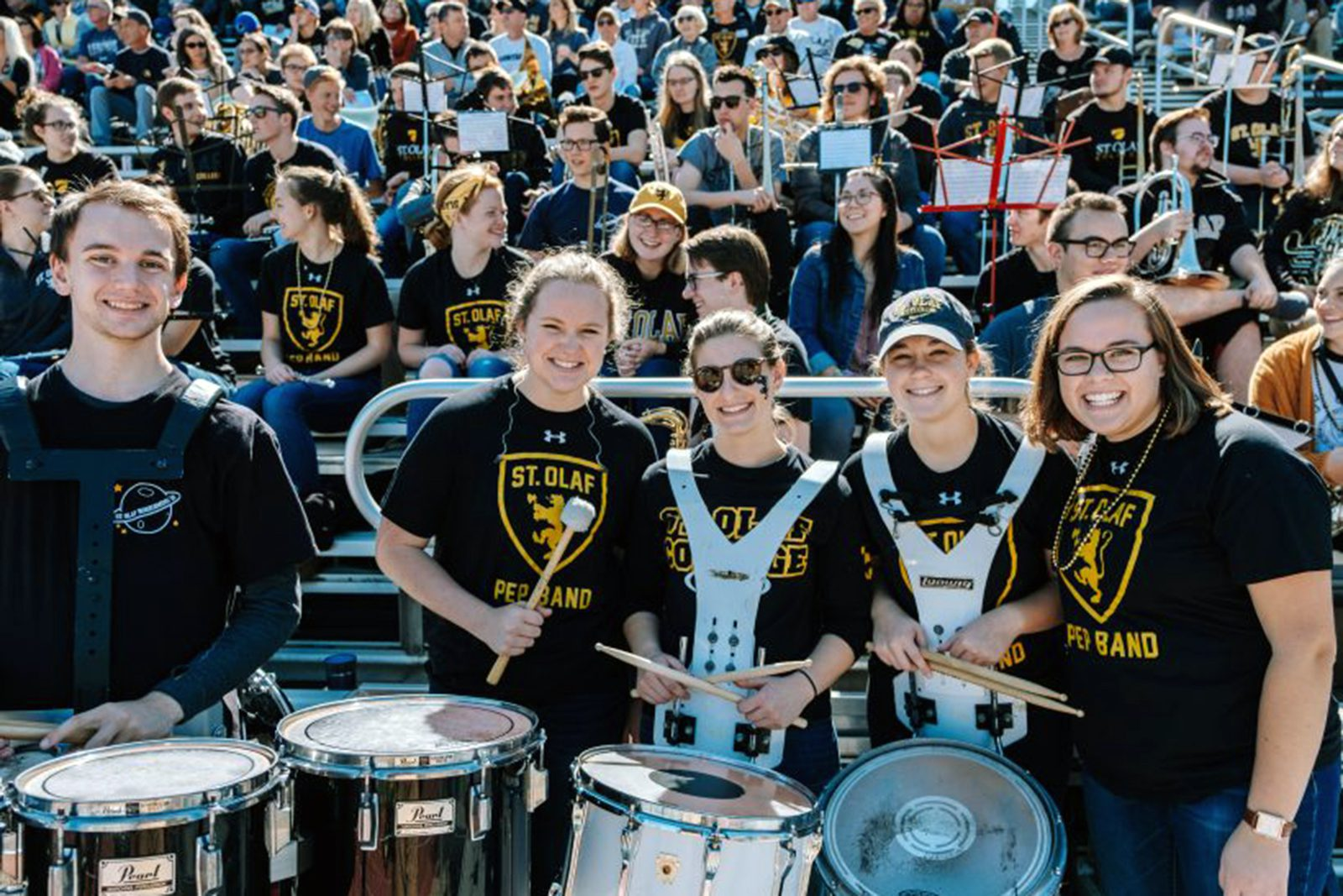 Students carrying drums smile in the foreground with students sitting in bleachers behind them.