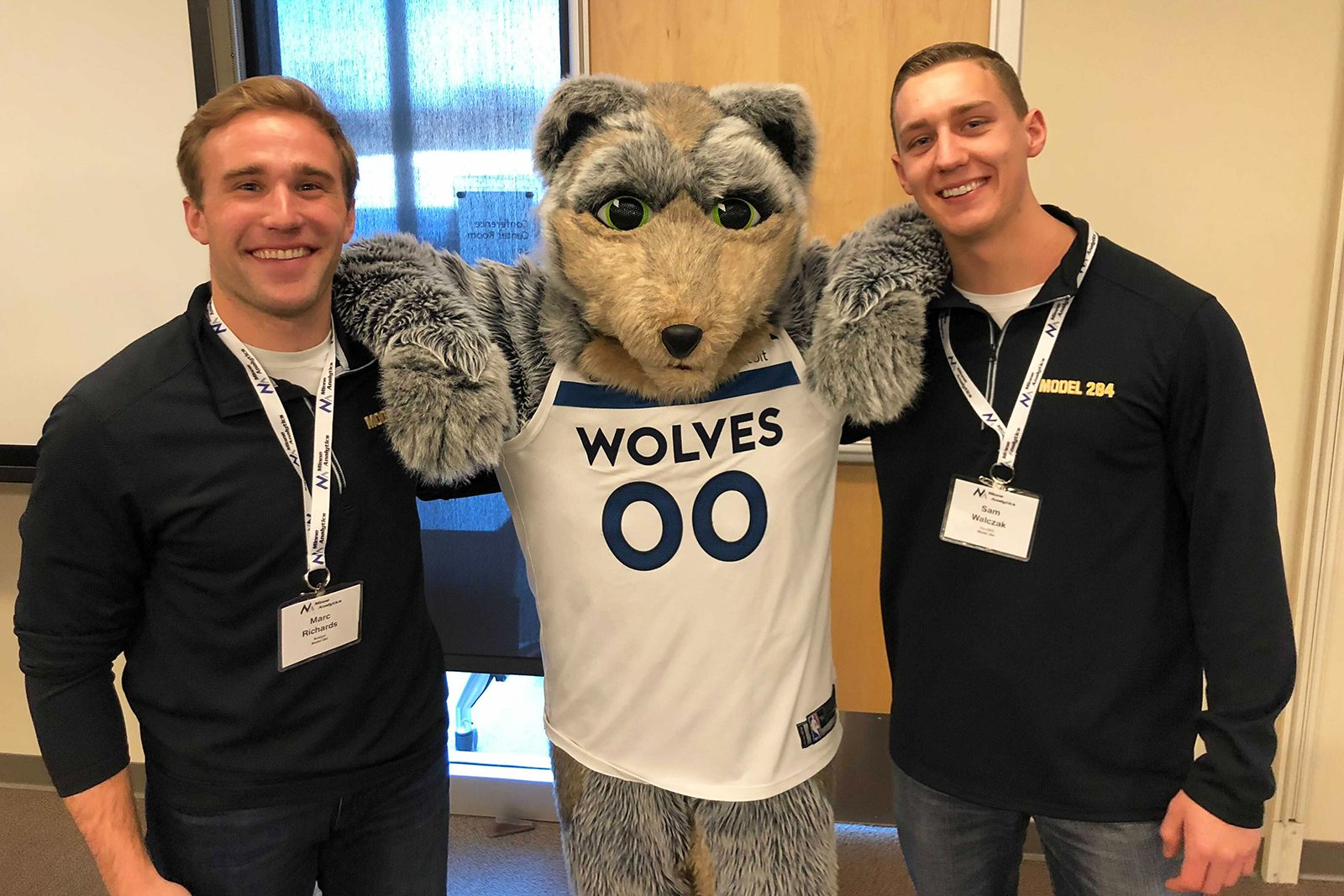 Marc Richards '16 (left) and Sam Walczak '14 (right), pictured here with Minnesota Timberwolves mascot Crunch the Wolf, are two members of the team that won the National Football League's Big Data Bowl.
