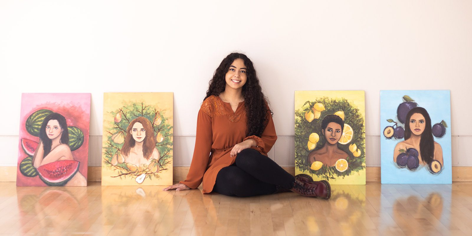 Amanda Rose '21 sits with FRUIT, her series of oil paintings. Photo by Lucy Gruidl.