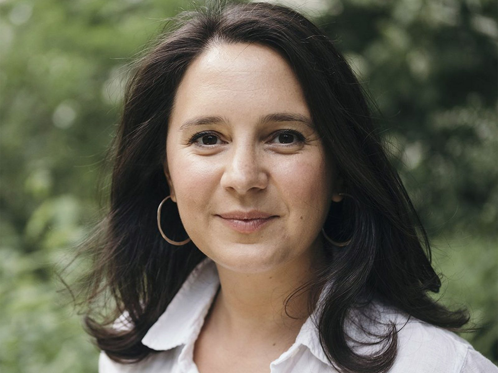 Portrait of Bari Weiss outdoors, with tree foliage in the background.