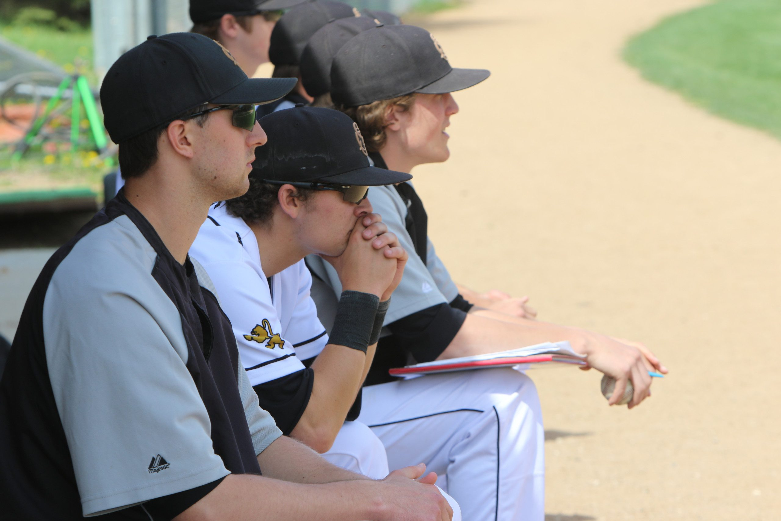 Anders Dzurak '13 (far left) in the dugout as a coach for the St. Olaf Baseball team.