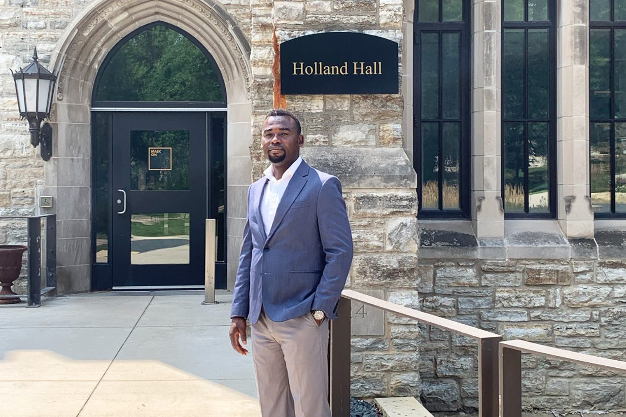 Assistant Professor of Economics Marcus Bansah outside Holland Hall, where he teaches classes in macroeconomics, international economics, and the economics of developing nations — three specialties that he's been able to blend into work both in and out of the classroom.