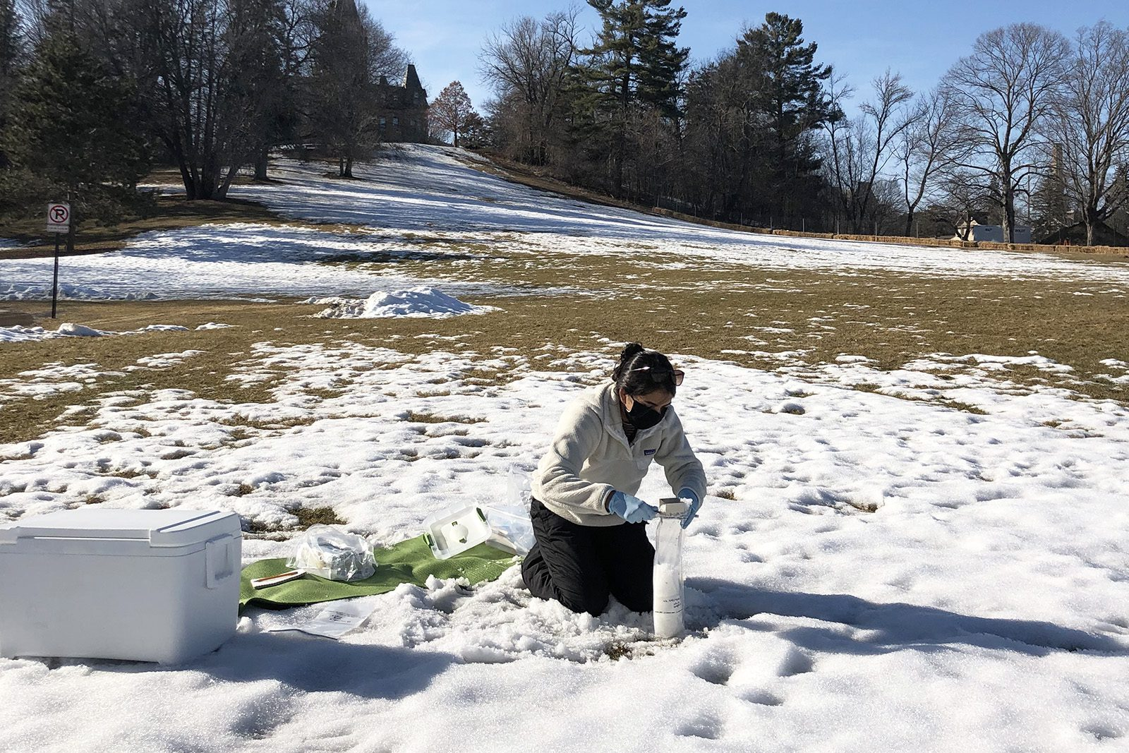 Kavya Devgun '21 collects snow samples for research near Old Main.