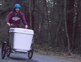 Man in 20s rides bike with container in front downhill