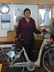 Mae Snaer poses behind bike in office