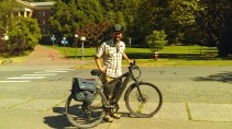 Tony Thompson posing behind electric bike in front of Edens Hall
