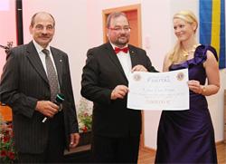 Präsident Mario Bielig bei der Scheckübergabe an die Sächsische Weinkönigin Anja Riedl, die ihn stellvertretend für den Lions Club Pirna entgegennahm. Links im Bild Lions-Vorstandsmitglied Gerd Müller, Moderator des Abends.