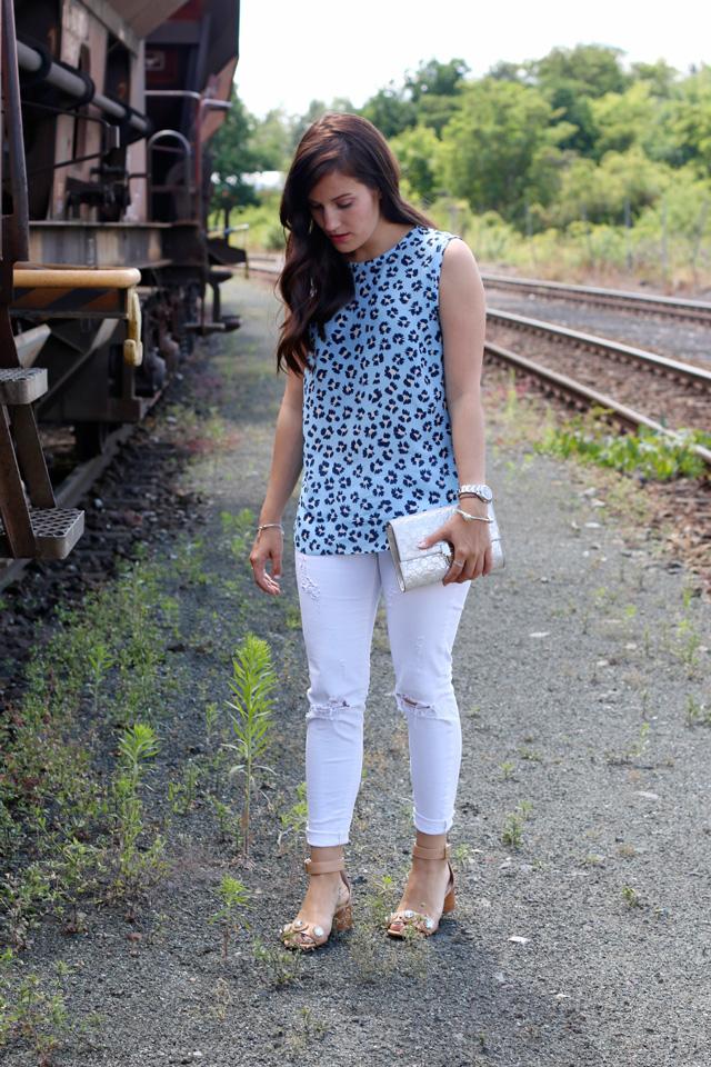 Joop Spring/Summer Kollektion 2015, Blaues Blumenshirt Seidenshirt, Weiße Skinny Jeans, silberne Clutch, Nudefarbene Sandalen mit Glitzersteinen