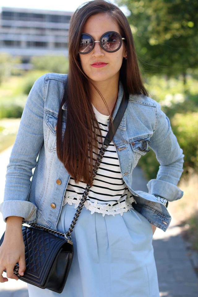 runde Sonnenbrille, Hippiesonnenbrille, Jeansjacke mit Chanelbrosche, gestreiftes Croptop, hellblauer Skaterrock, Boy Bag