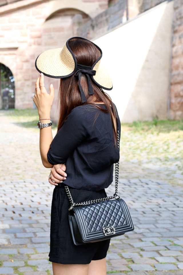 Schwarzer Jumpsuit, schwarzer Playsuit, Chanel Boy Bag, Strohhut, Sommerhut, Sommerlook mit Hut