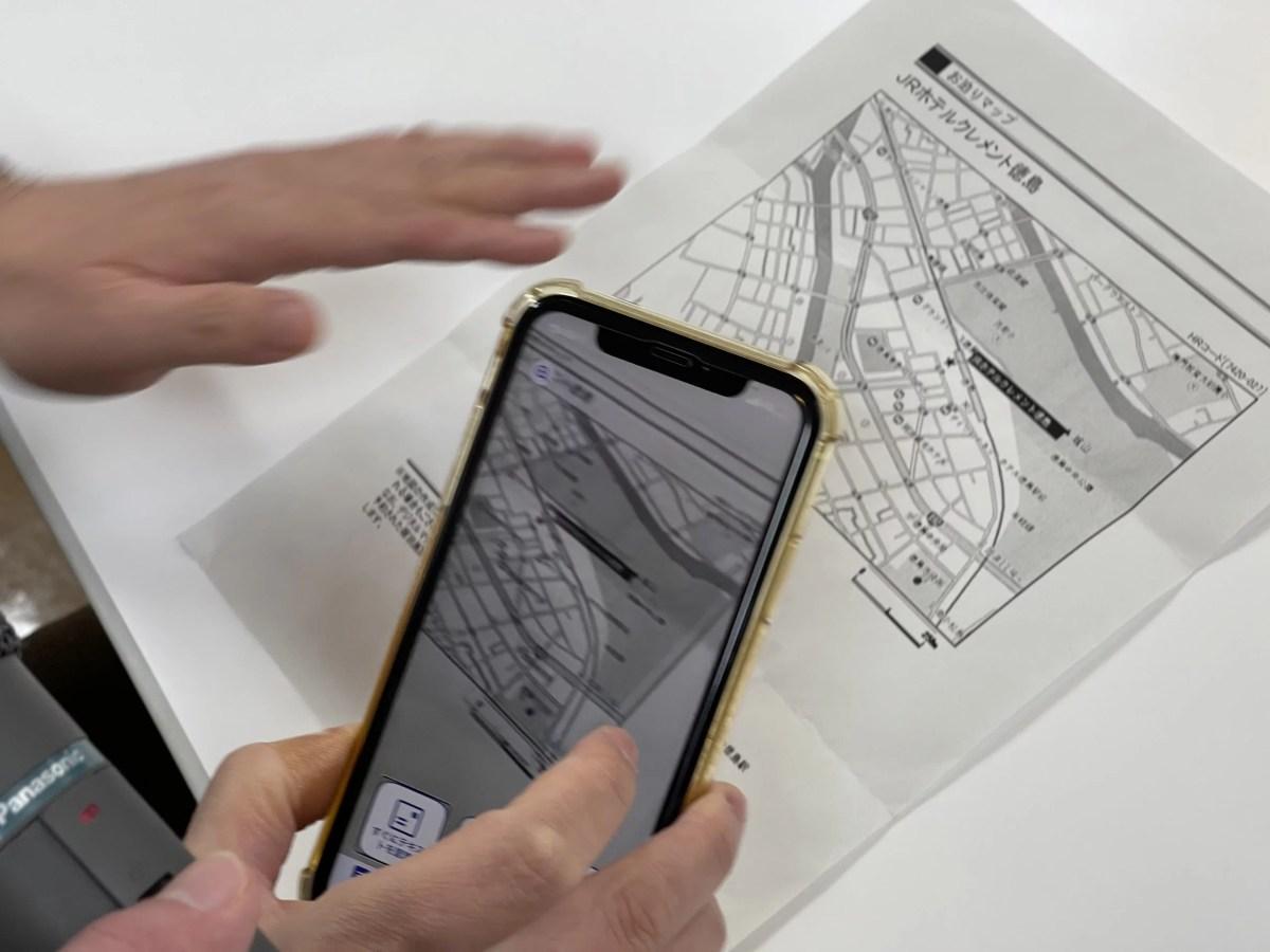 紙の情報をiPhoneのアプリで読み取る様子