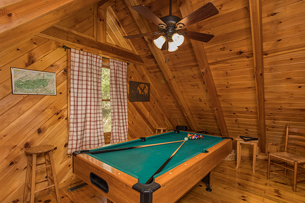 A green felt pool table in the loft at Cabin in the Woods. A Pigeon Forge cabin rental