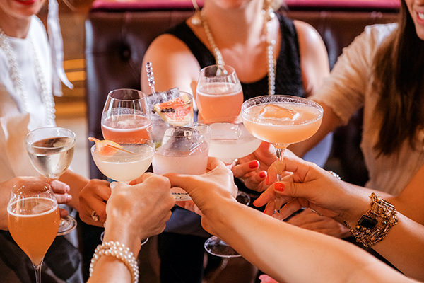 a group of women holding alcoholic drinks