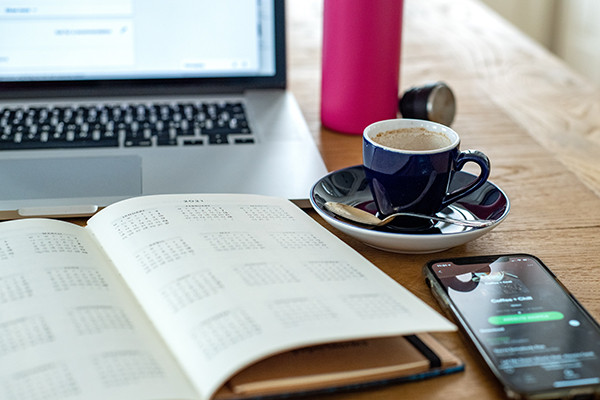 a day planner, computer, phone, and coffee