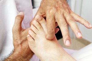 A reflexology therapist manipulates by placing pressure on a patient\'s foot.