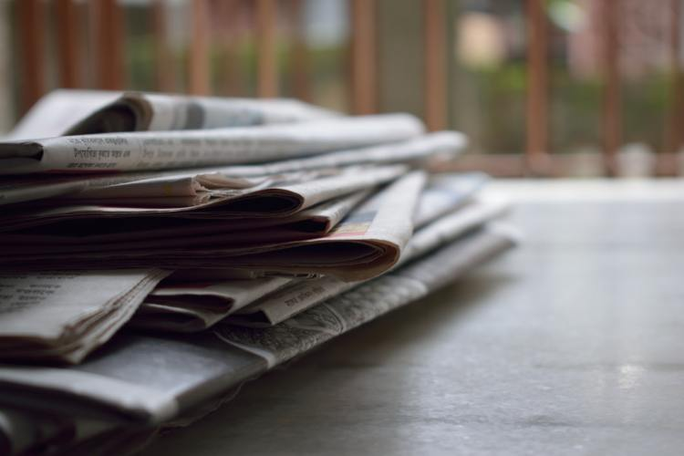 A stack of newspapers sitting on the left side of a desk.