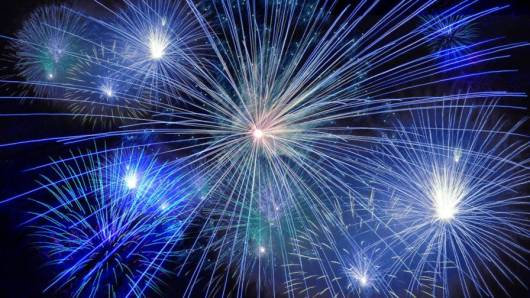 Blue and purple fireworks exploding in the night sky.