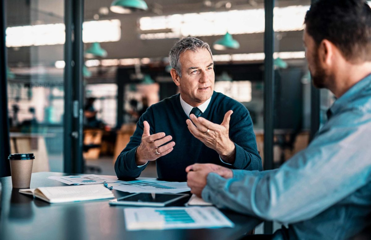 Shot of a mature businessman having a discussion with a colleague in an office