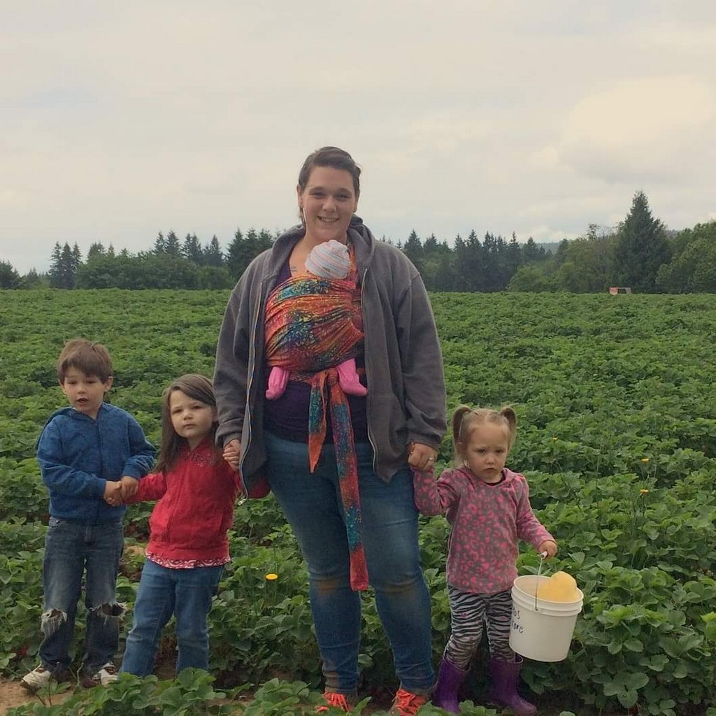 The author cared beautiful for her four children in spite of serious postpartum anxiety. The author stands in a field facing the camera. Her baby is wrapped on her front in a colorful Wrapsody Hybrid Jennifer. She holds the hands of her older children.