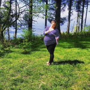 The author, very pregnant, stands in a grassy clearing. She is looking away from the camera toward the bubble solution and wand in her hands.