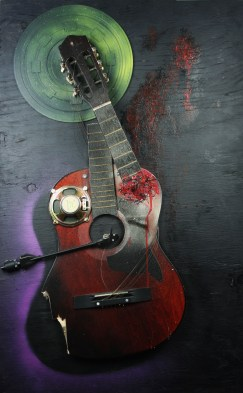 """""""Christine"""" 2010, 24"""" x 38"""" x 5"""" guitar, mixed media on plywood. Christine is a three dimensional assemblage consisting of a warped guitar, a record player's arm and the internal workings of a speaker."""