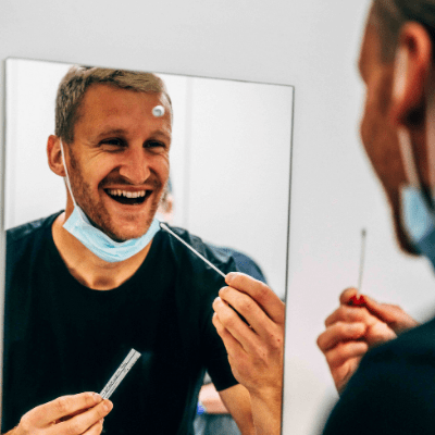 image of man smiling holding a swab