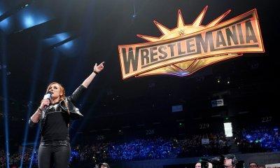 Becky Lynch apontando para o grande logo da Wrestlemania