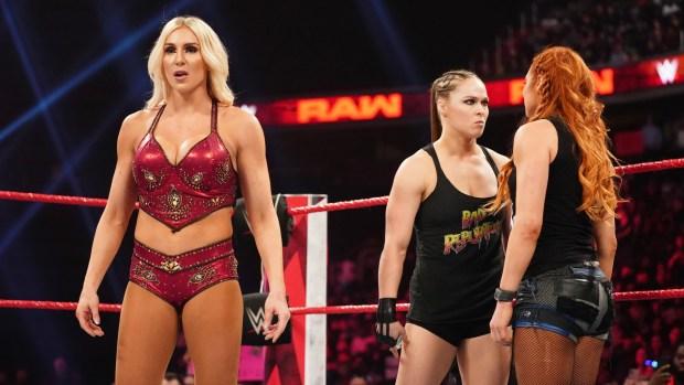 Becky Lynch e Ronda Rousey se encaram ao fundo, enquanto Charlotte olha fixamente para as adversárias.
