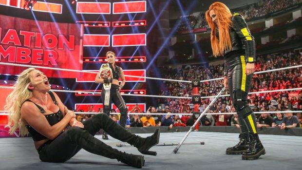 Becky Lynch segura um par de muletas diante de Charlotte Flair sentada com dores no ringue, enquanto Ronda Rousey acompanha ao fundo.