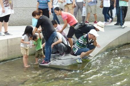 homem bebendo água de córrego em Seul