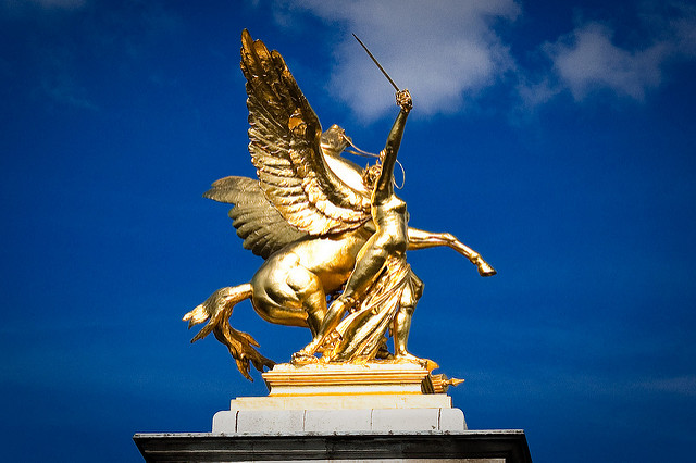 Image, Golden statue of sword-wielding person beside a winged horse