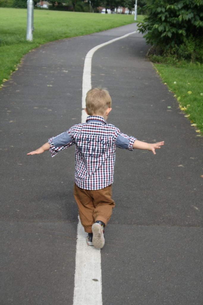 Image, boy walking along centre line with arms out.
