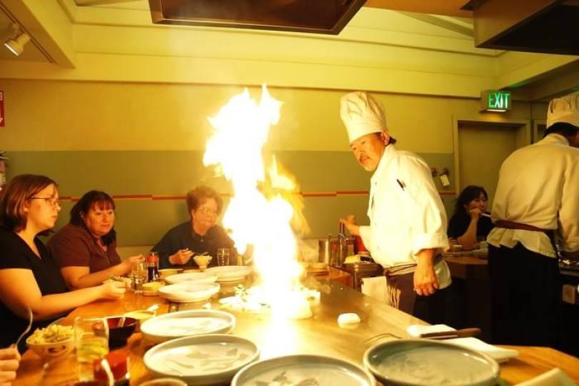 Шеф-повар готовит еду прямо напротив клиентов
