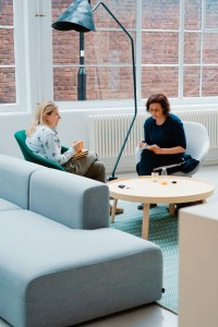 two women talking on couch in commercial building