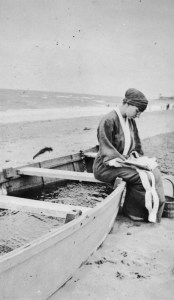 Woman Sitting on a Beached Boat - THE PUBLC DOMAIN