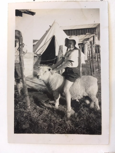 child sitting on a ram in front of an old army tent