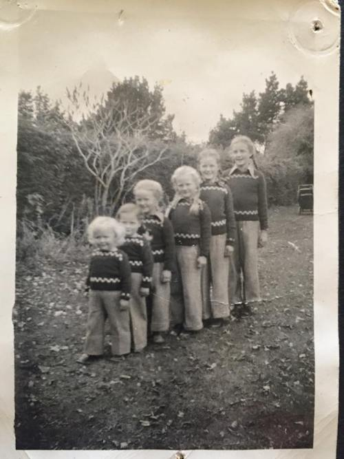 Photo of 6 girls aged 3–11 in plaits, slacks and hand-knitted jerseys in a rough garden