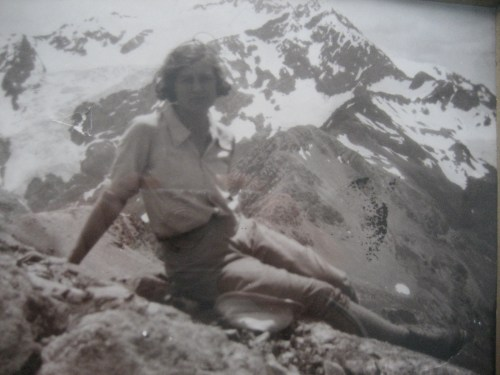 Celia Taylor relaxing on a mountain top in climbing gear.