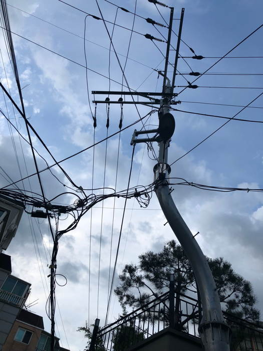 Photo of a curvacious utility pole with a load of wires.