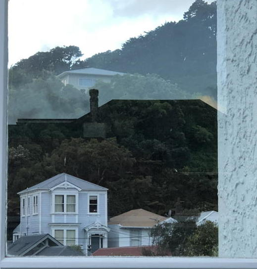 Photo of houses on a hill plus the shadow of another house