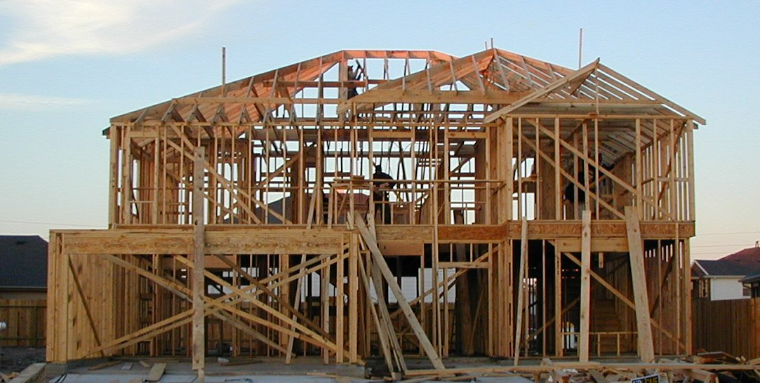 Photo of a wooden framed house under construction.