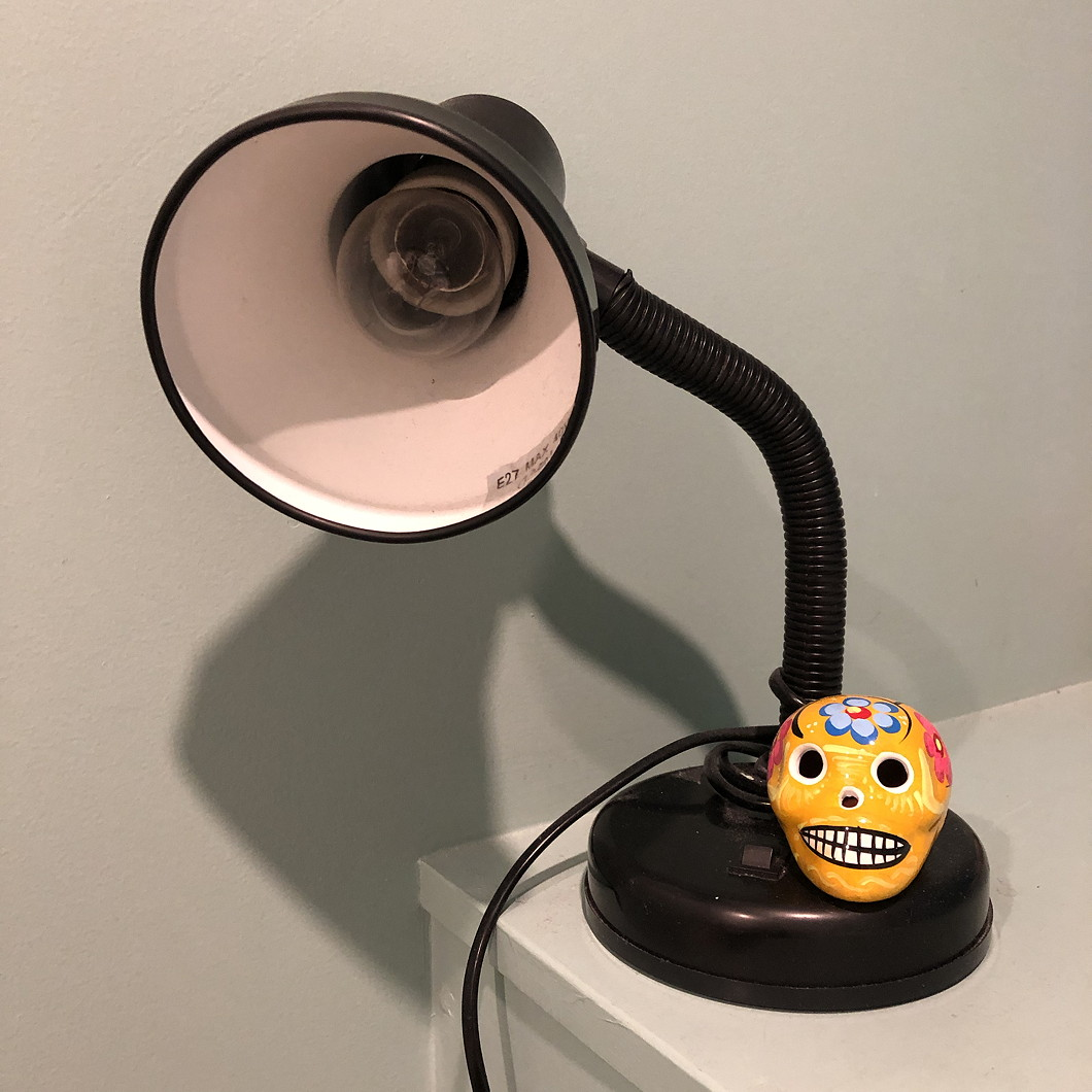 A small Mexican pottery skull perching under a bedside lamp