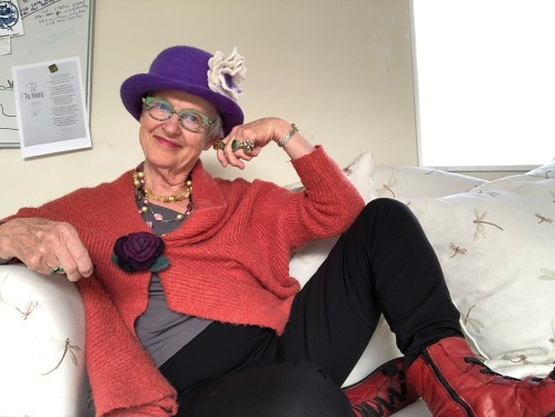 Old woman wearing purple hat, red sweater, purple brooch, red boots, five rings and two necklaces.