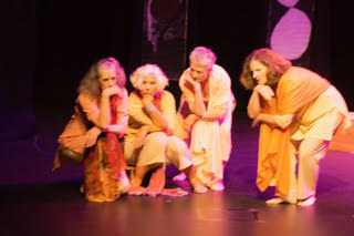 Four older women in a thoughtful dance pose on stage