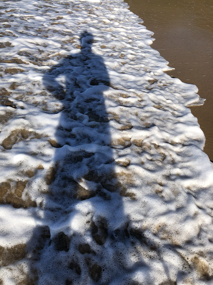 Photo of sea foam with shadow of a person standing.