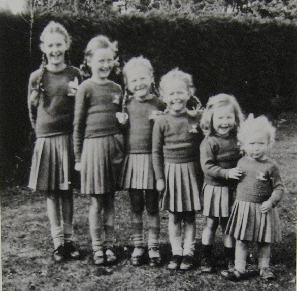 old snapshot of six girls from 3 to 11 years old dressed alike and most giggling