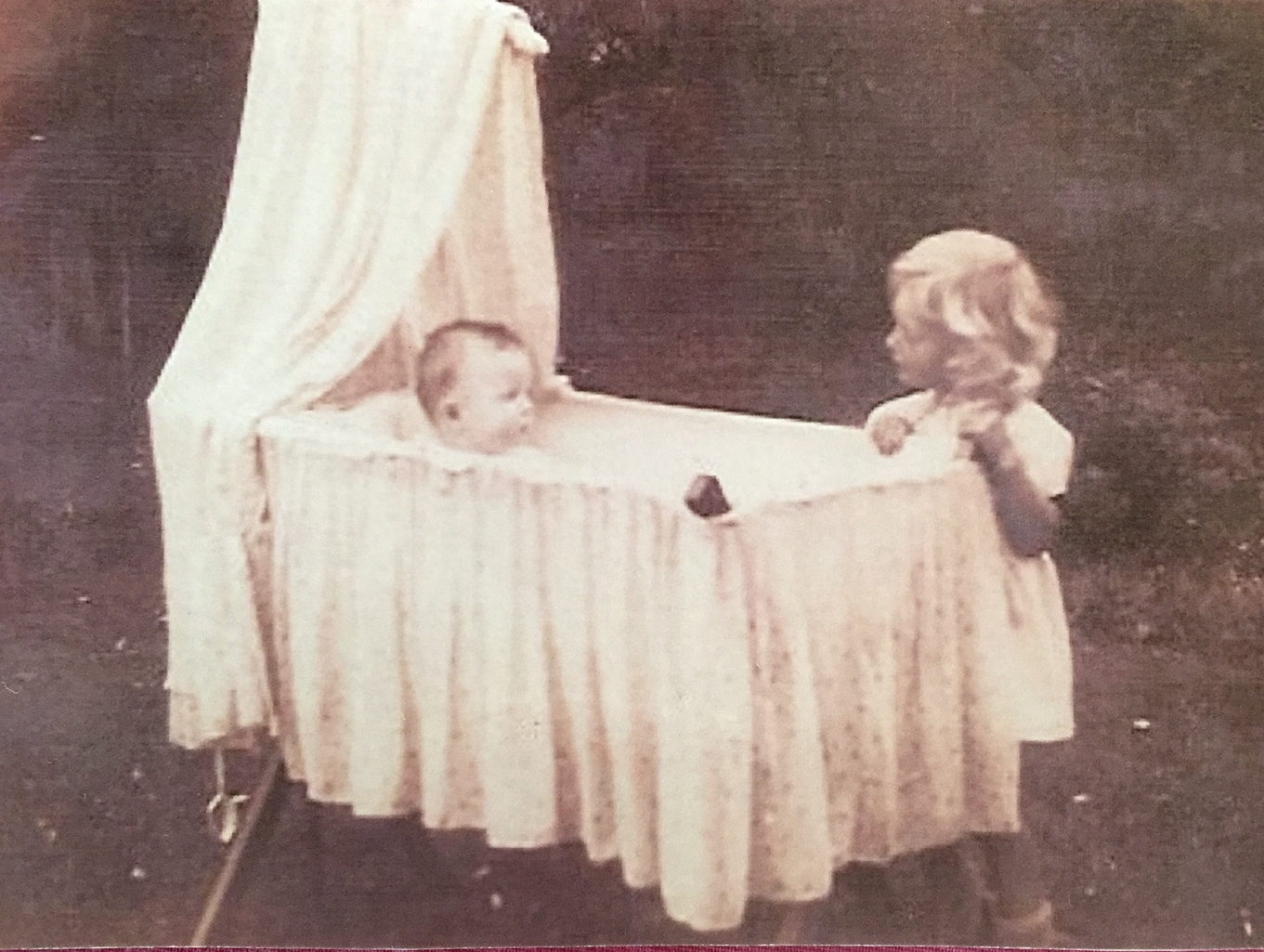 Old photo of a baby sitting in a draped bassinetobserved by a little girl