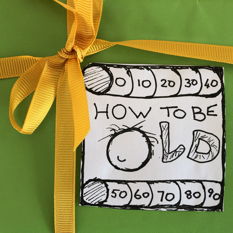 HOW TO BE OLD podcast logo on green paper tied with a yellow ribbon