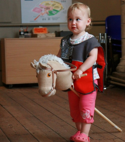 Child riding a toy wooden hobby horse